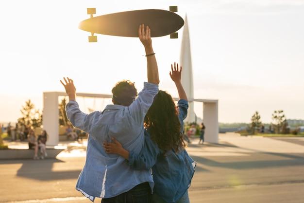 일몰을 바라보는 세련된 젊은 커플 포옹 스케이트보드 행복한 소녀와 사랑에 빠진 남자는 자유를 즐긴다