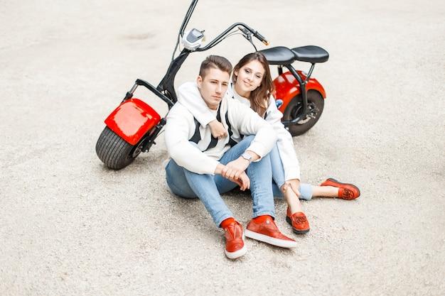 Стильная молодая пара в модной одежде сидит возле красного электрического велосипеда