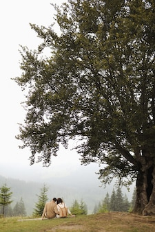 Stylish young couple in love in the foggy mountains. man and woman are sitting under a large old tree and hugging
