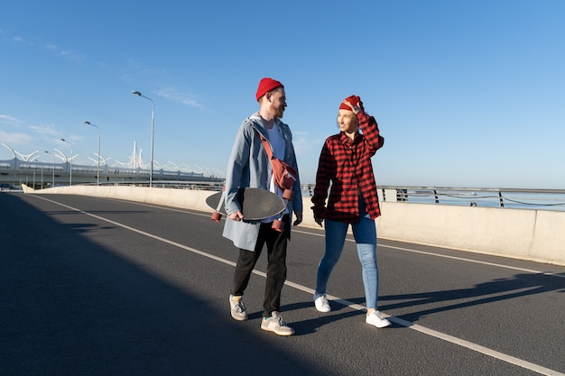 Stylish young couple of male and female walk together on bridge after longboard skating on bridge