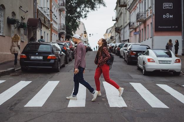 세련 된 젊은 부부 야외 포즈. 긴 머리를 가진 여자와 모자에 다름으로 젊은 남자. 행복한 젊은이들이 도시 주변을 걷고 있습니다. 초상화. 확대.