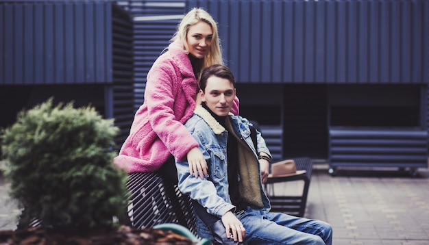 Stylish young couple sitting on a bench near a shopping center