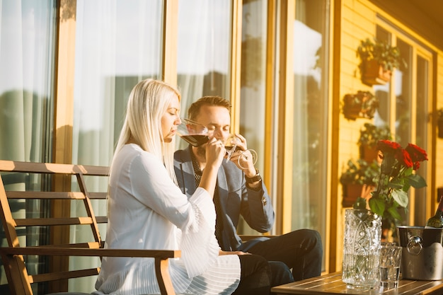 赤ワインを飲むパティオに座っているスタイリッシュな若いカップル