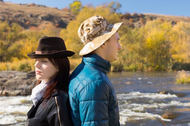 流れの速い田舎の川を背景に屋外に背中合わせに立っているスタイリッシュな若いカップル