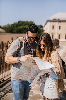 Stylish young couple on vacation looking at map