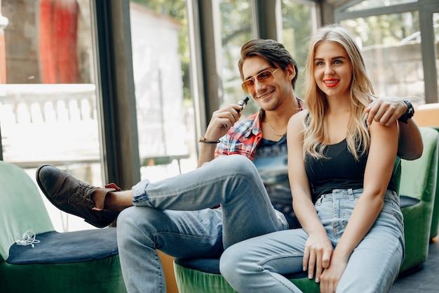 Стильная молодая пара с вейпом в кафе