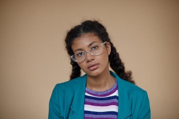 포즈를 취하는 동안 청록색 블레이저와 줄무늬 스웨터를 입은 차분한 얼굴로 보면서 안경을 쓰고 머리띠를 가진 세련된 젊은 곱슬 어두운 피부 여성