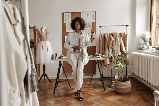 Stylish young curly dark-skinned woman in white pants, jacket and blouse leans on desk in fashion designer office, holds coffee cup and laptop