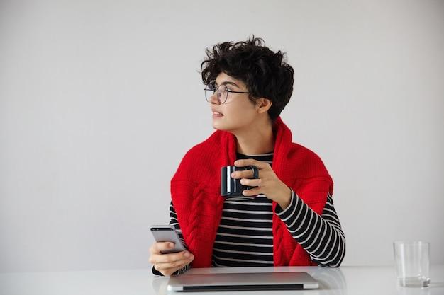 Стильная молодая темноволосая кудрявая симпатичная женщина с короткой модной стрижкой сидит за столом с современным ноутбуком и делает перерыв в работе с чашкой чая, изолированные на белом фоне