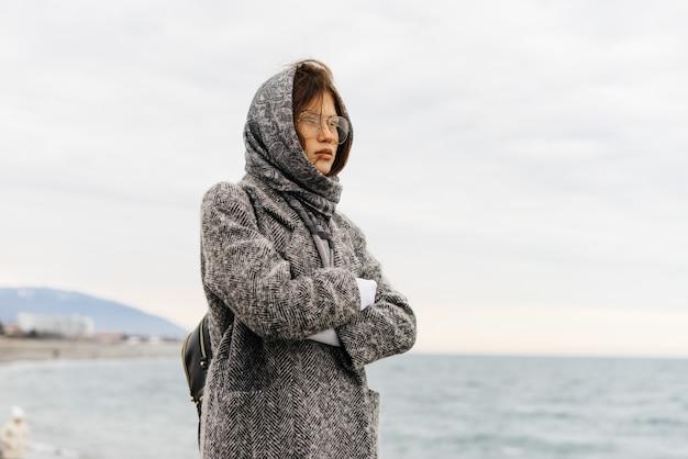 Стильная молодая темноволосая девушка в очках, платок на голове, прогулки у моря, пасмурная погода