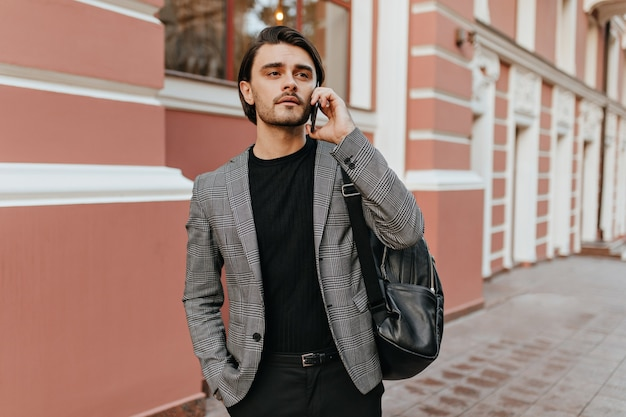 Stylish young dark-haired man in black t-shirt and grey blazer talking on phone against light city building wall and looking away