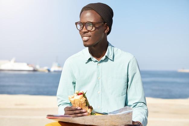 Стильный молодой мечтатель с картой сидит на набережной на фоне спокойного моря