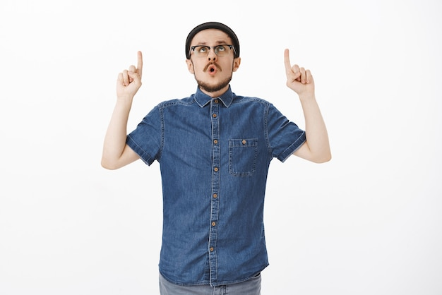 Stylish young european male with beard and moustache in hat and glasses folding lips saying wow pointing and staring up excited over white wall