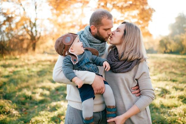 スタイリッシュな若い家族が赤ちゃんを手で押し、日当たりの良い公園でキスします。