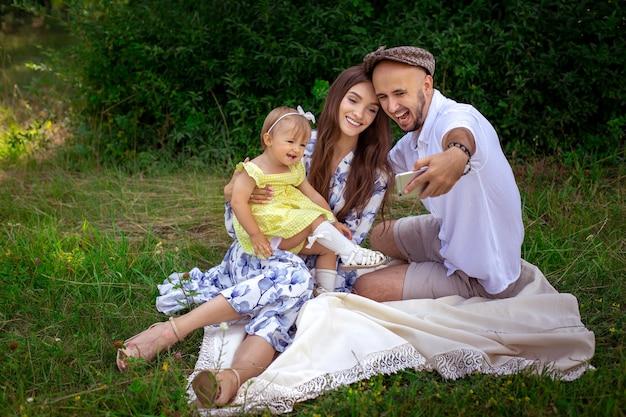 Стильная молодая семья делает селфи на пикнике. родители с маленькой дочкой фотографируют на мобильный телефон в зеленом парке