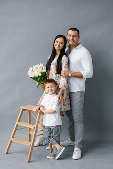 Stylish young family: mom, dad and four-year-old son stand near a wooden stepladder and smile, isolated on a white background. happy family