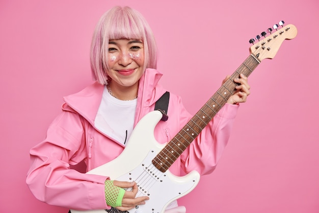세련된 젊은 femae guiratist는 재킷을 입고 장갑은 흰색 일렉트릭 기타에서 록 음악을 연주하며 콘서트를 준비합니다.