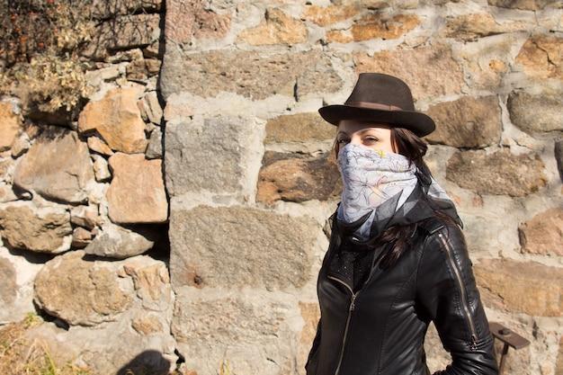 彼女の顔を隠すためにスカーフとコピースペースのある古い石の壁に立っている流行の帽子を身に着けているスタイリッシュな若い女性の盗賊