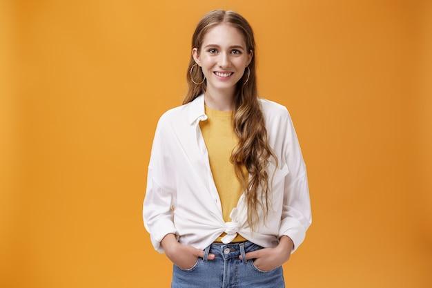 スタイリッシュな若い女性デザイナーは、オレンジ色の壁にポーズをとる黄色のtシャツの上に流行のブラウスを着て、カメラに向かって楽しく笑顔で自信を持って手をつないで買い物をする友人を助けたいと考えています。