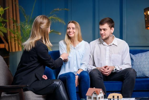 Стильная молодая женщина-риэлтор дает ключ от новой квартиры, дом для счастливой кавказской пары.