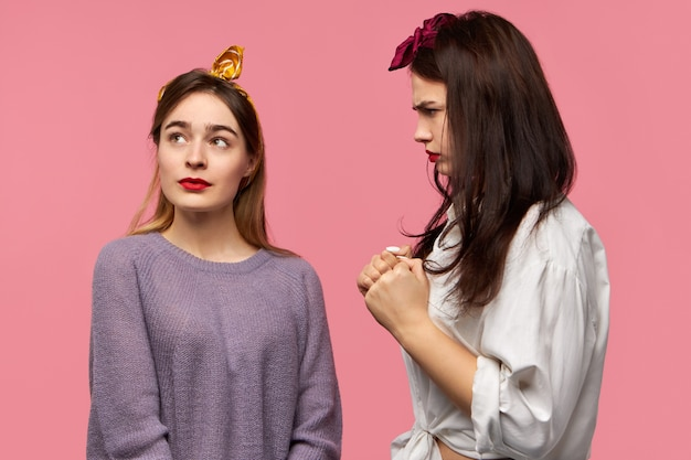 Стильная молодая женщина трясет кулаками, угрожает подруге, которая смотрит вверх с небрежным выражением лица, как будто игнорируя ее угрозу. сердитая недовольная женщина, выражающая отрицательные эмоции