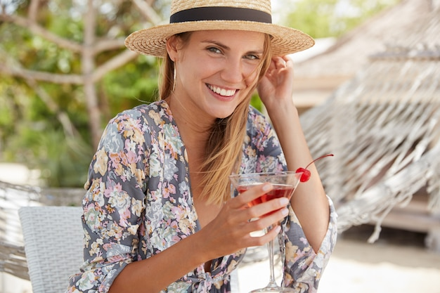 スタイリッシュな若い女性は夏の麦わら帽子とファッショナブルなシャツを着て、新鮮なチェリーカクテルを手元に置いており、屋外カフェで自由な時間を過ごすことができます。外の冷たいジューシーな飲み物で愛らしい女性ポーズ
