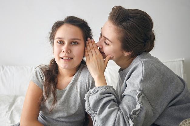 魅了された妹の耳元に何かをささやき、秘密を共有するスタイリッシュな若い女性。