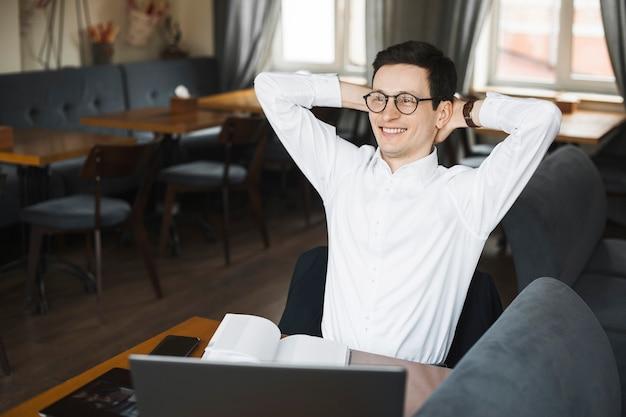 흰 셔츠를 입은 세련된 젊은 프리랜서는 노트북의 커피 숍에서 일하는 동안 웃고 등을 뻗는다.