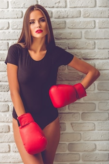 Stylish young girl in black bodysuit and boxing gloves.