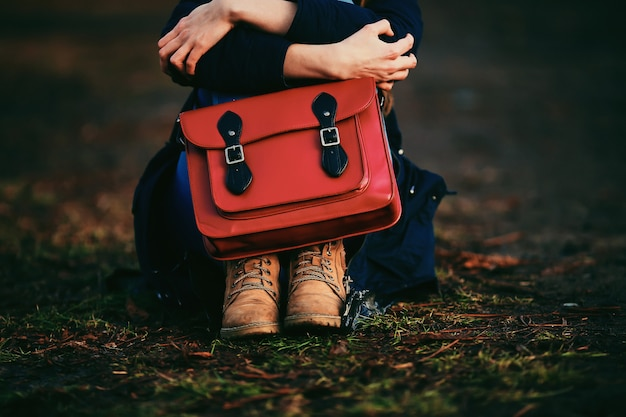 Stylish young girl in brown shoes and warm coat sits in the park with a red bag