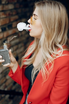 Stylish young girl  in a city with vape