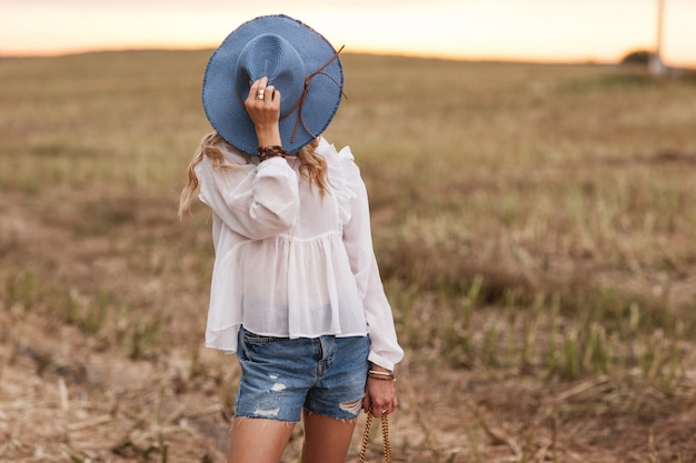 Stylish young girl dressed in ethnic style stands in the field and covers her face with a hat