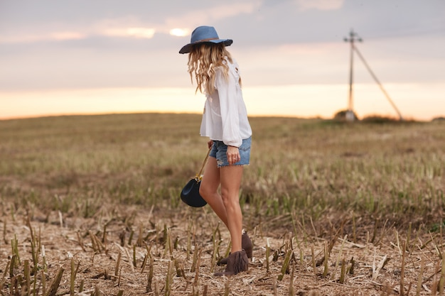 Stylish young girl dressed in ethnic style stands in a field