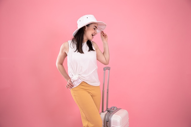 Stylish young girl in a hat with a valise on a pink background. summer vacation and travel concept copu space.