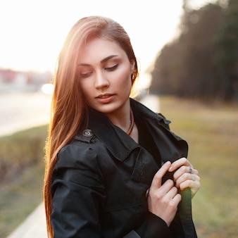 Стильная молодая девушка в черном пальто позирует в солнечный день