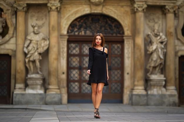 Стильная молодая девушка в черном платье на улице города брно утром. чехия.