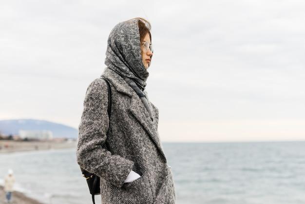Стильная молодая девушка в сером пальто и очках гуляет у моря, наслаждается природой и пасмурной погодой