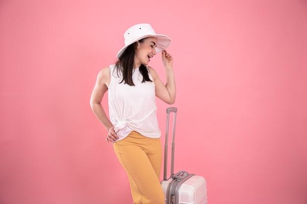 ピンクの背景にスーツケースと帽子のスタイリッシュな若い女の子。夏休みと旅行のコンセプトコプスペース。