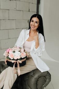 스튜디오에서 꽃의 부케와 흰 셔츠에 세련된 어린 소녀