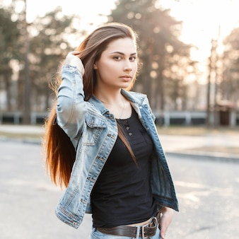 Стильная молодая девушка в модной джинсовой одежде поправляет длинные волосы на закате