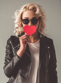 Stylish young girl in leather jacket and sun glasses.