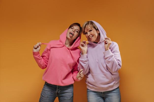 Ragazza alla moda in felpe con cappuccio rosa che sbatte le palpebre, mostrando le lingue e in posa con la vecchia in abiti lilla su sfondo arancione.