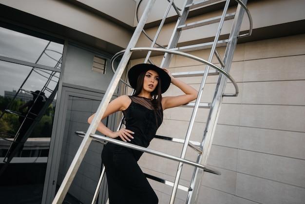 Стильная молодая девушка позирует в шляпе на пожарной лестнице бизнес-центра. мода.