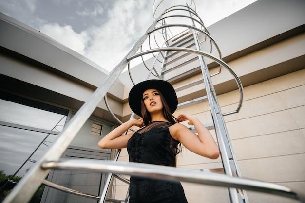 Стильная молодая девушка позирует в шляпе на пожарной лестнице