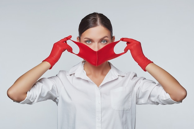 Stylish young girl puts on red face mask and gloves.