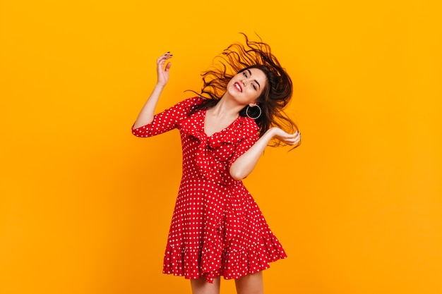 Stylish young girl in red short dress plays hair. portrait of brunette in hoop earrings on yellow wall.
