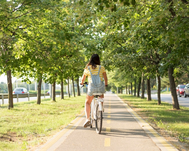Stylish young girl riding bicycle