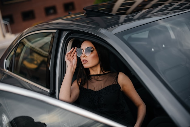 Stylish young girl sitting in a business class car in a black dress. business fashion and style