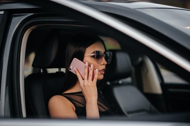 Стильная молодая девушка сидит в машине бизнес-класса в черном платье и разговаривает по телефону. деловая мода и стиль.
