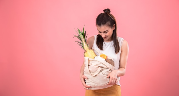 Stylish young girl smiling and holding an eco bag with exotic fruits